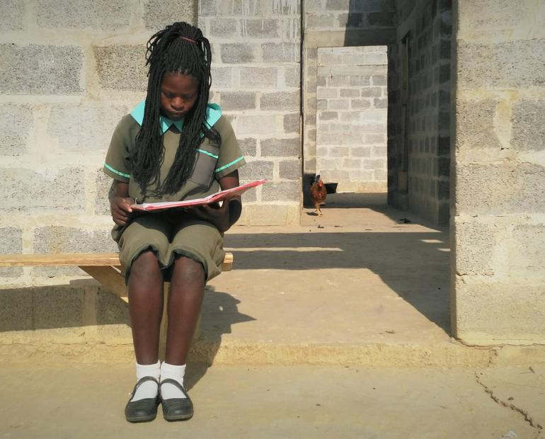 Beauty, book in hand; seated outside her home, studying before class.