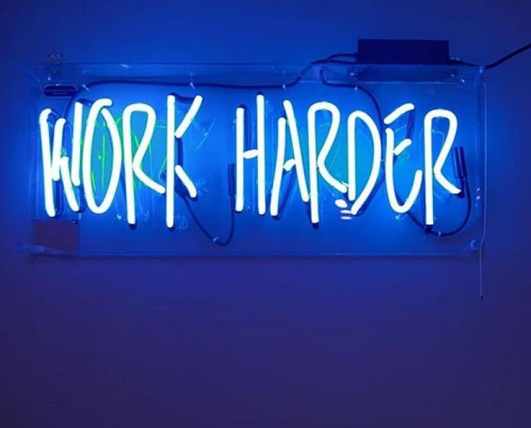 neon sign with the words work harder