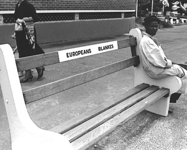 A black man sitting on a bench written Europeans only in Apartheid South Africa