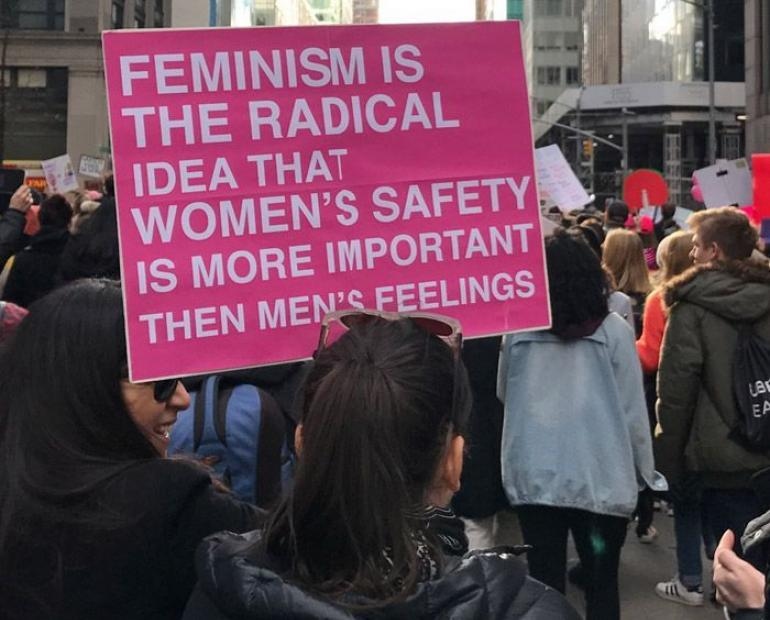 "A woman at a protest holding a sign saying ""feminism is the radical idea that women's safety is more important then men's feeling"""