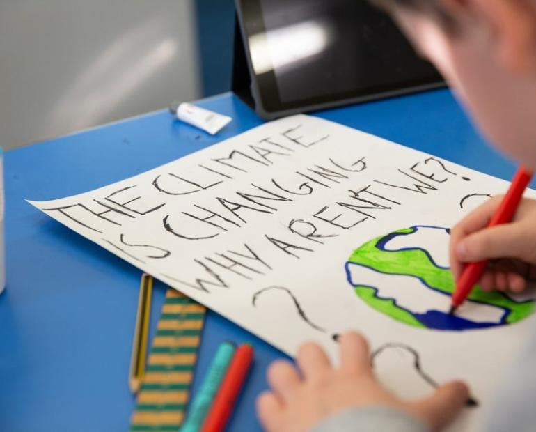 "On 7 February 2020, a young boy takes part in a lesson about climate change and environmental activism at Craigentinny Primary School in Edinburgh, Scotland. As a creative task in this lesson, the teacher asks her pupils to create their own protestsigns. This pupil writes, ""THE CLIMATE IS CHANGING WHY AREN'T WE?"""