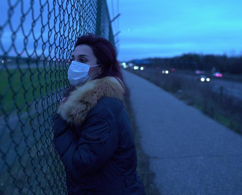 White girl wearing a face mask standing in front of a fence