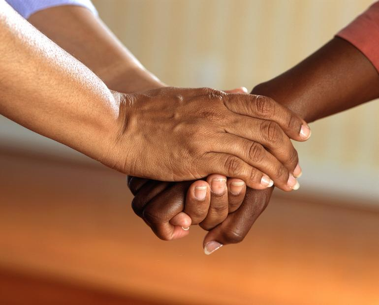 Focus on two people's hands. One person is holding the other's hands in a supportive way.