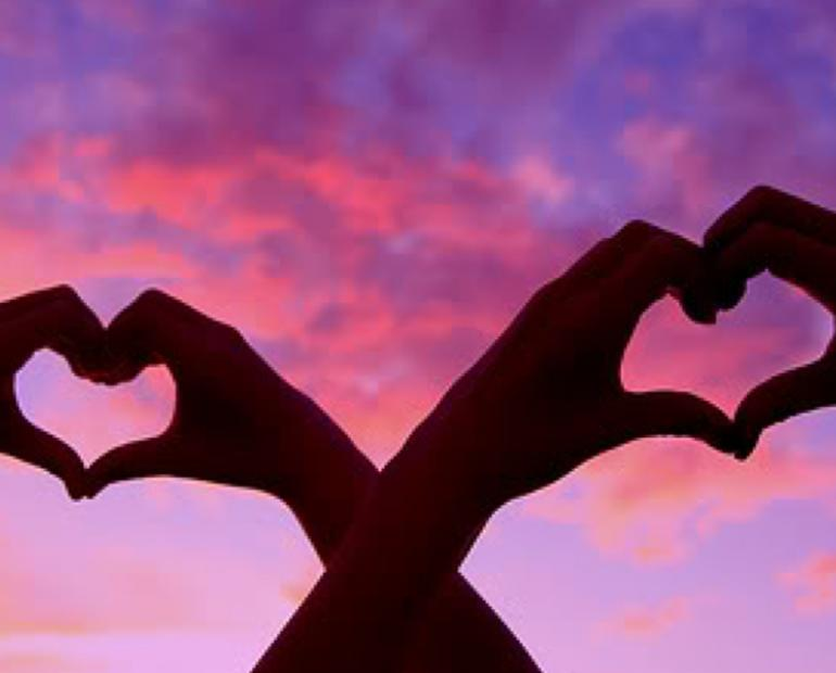 Hearts made with hands and a sunset