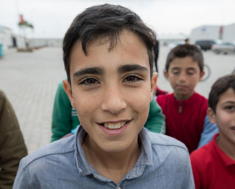 Children at the Kahramanmaras Temporary Accommodation Center in Turkey, children play outside. The camp currently hosts more than 11,000 Syrian refugees, half of them children. It offers schooling for 3,700 children and training opportunities for young people.