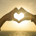A person makes a heart shape with their hands against a setting sun