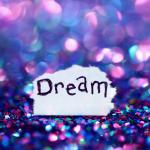 Dream written on a piece of paper in a pile of purple and blue confetti