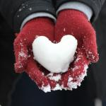 Someone with read gloves holding snow shaped into a heart.
