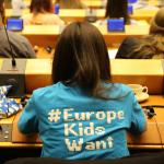 "A girl sits in a conference hall wearing a t-shirt with the words ""Europe Kids Want"" on the back"