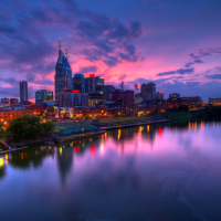 A picture of a purple sunset, with a skyline and a reflection over a waterfront.