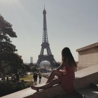 A picture of me sitting on the stairs facing the Eiffel Tower in Paris, France.
