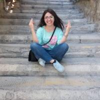 A girl sitting on old stairs and laughing