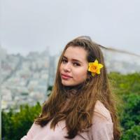 Chica rubia oscuro con flor amarilla en el la oreja, usando un suéter de cuello tortuga rosa pálido y el fondo de la fotografía es la ciudad de San Francisco.