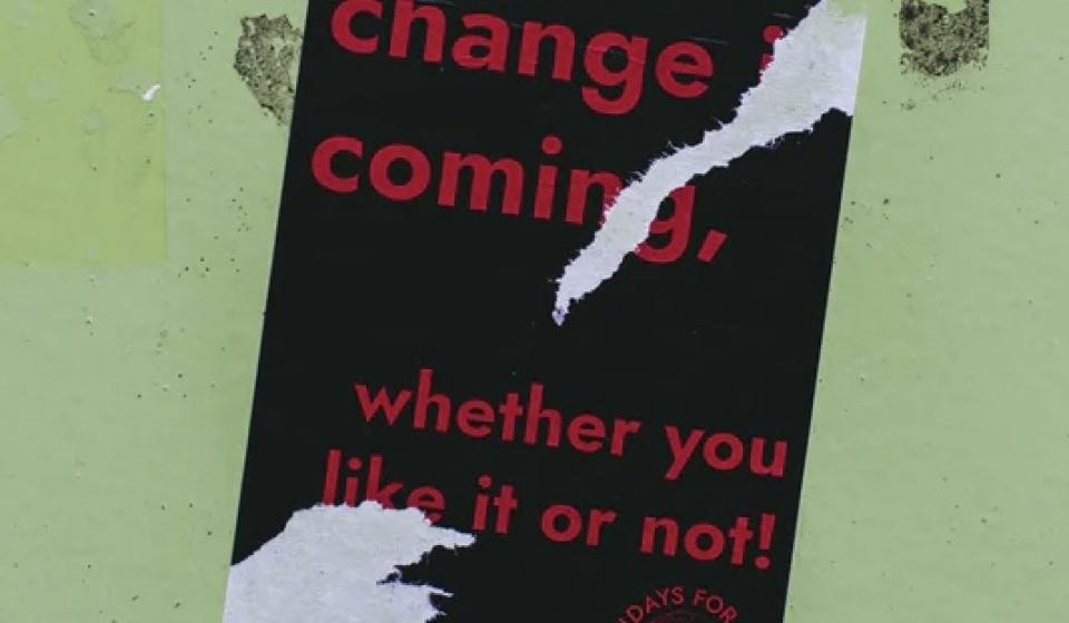 A poster which says, 'change is coming, whether you like it or not!'