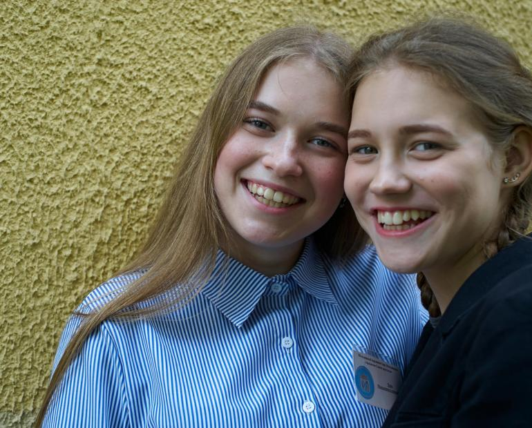 Two girls smile at th camera.