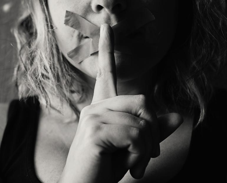 A woman holds a finger to her mouth, which is taped over