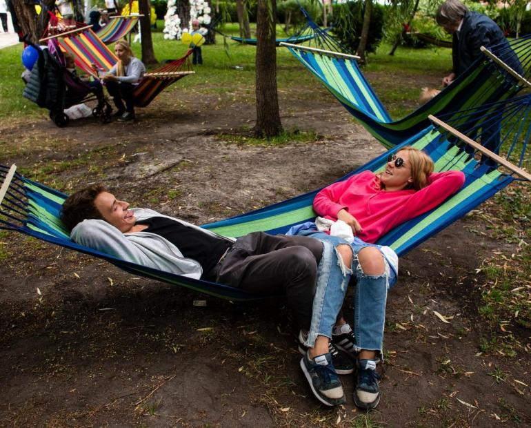 Two young people share a hammock in a park.