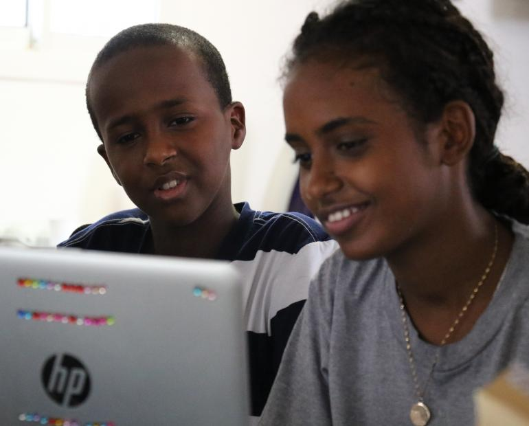 Two young people follow an automated coding programme