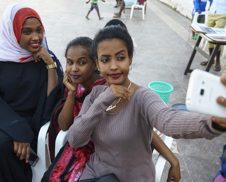 Three young girls take a selfie during a life skills training session.