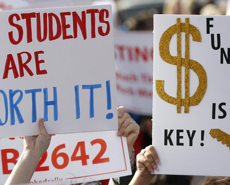 two protest signs that read our students are worth it and another that reads funding is key