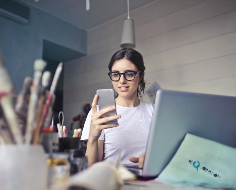 woman in white shirt using smartphone