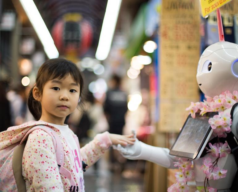 A little girl shaking a hand with a robot