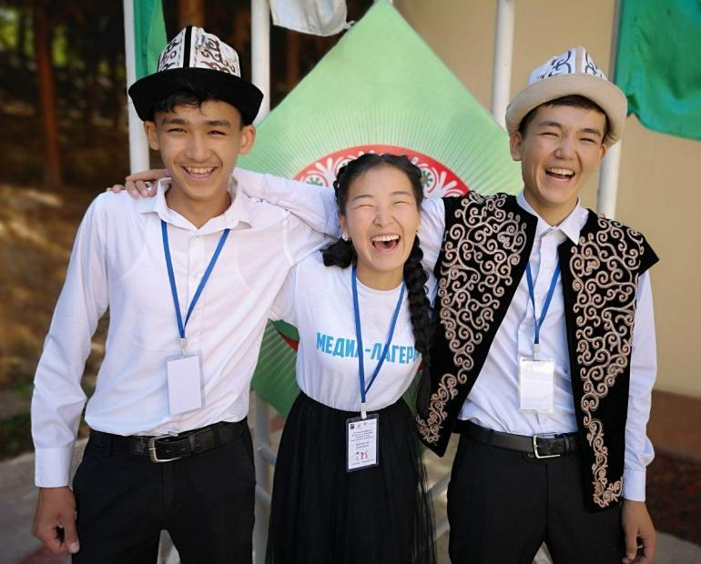 Three young people smile and laugh while standing side by side.