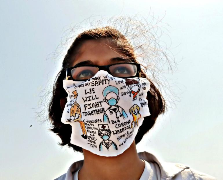 /A girl wearing a homemade mask painted with thanking messages during COVID19 for healthworkesrs, police and more.