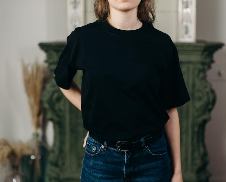 Person wearing black T-shirt and denim jeans
