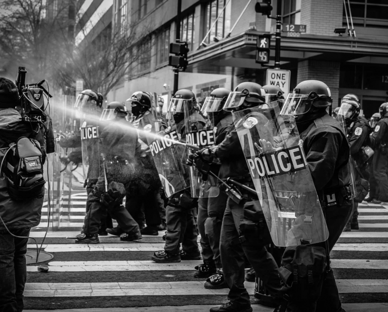 Black and white picture of protest, with police who have shields and water cannons