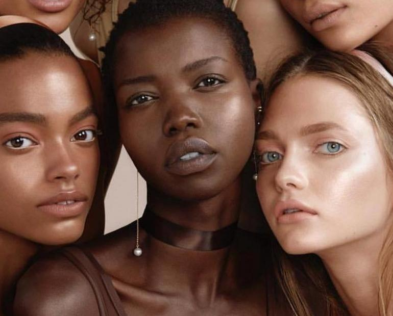 A picture with 4 females of different skin shades.