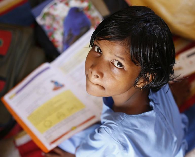 Young Indian girl with school book in front of her looking up.