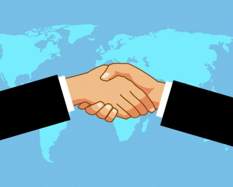 Picture symbolizing trust and brace through a handshake over picture of world