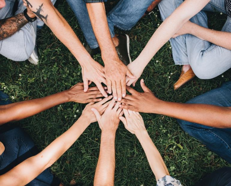 A group of people putting their hands together in a circle
