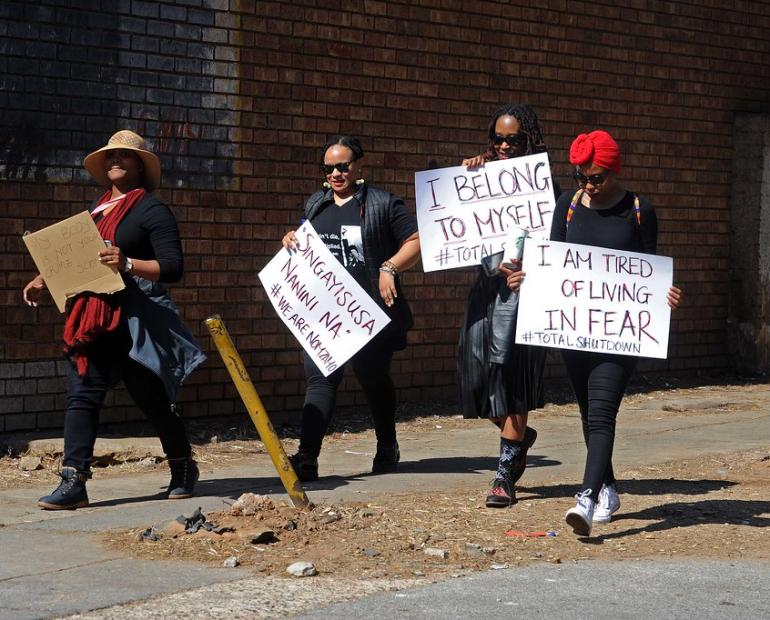 A picture of South African women walking whilst holding posters against GBV.