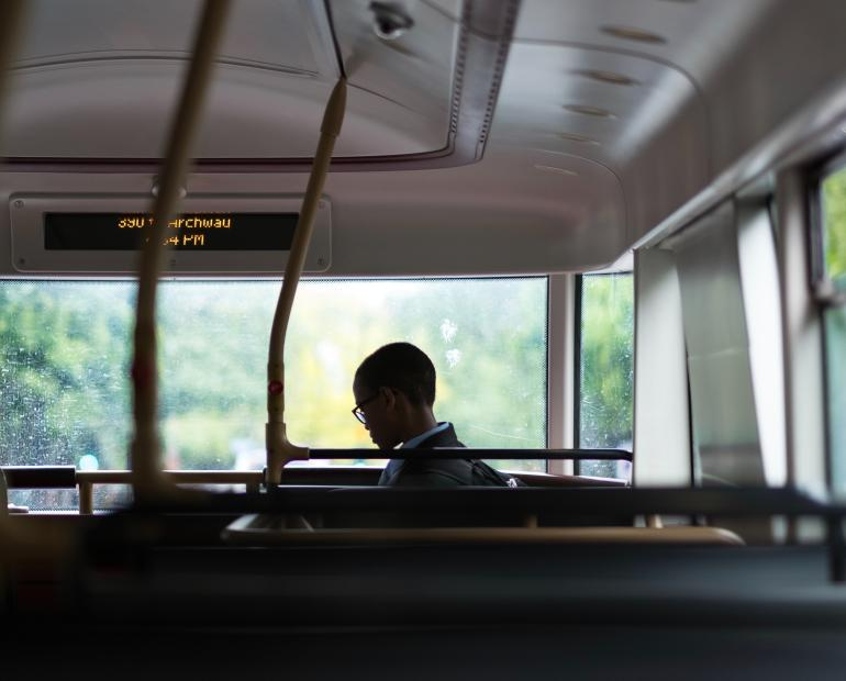 Black child gets onto an empty bus.
