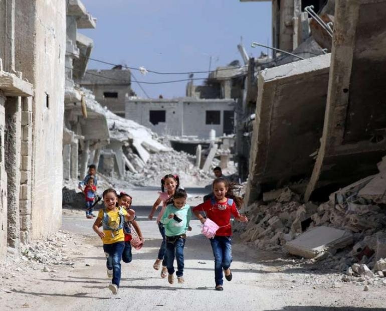 Children running amid a war destructed street