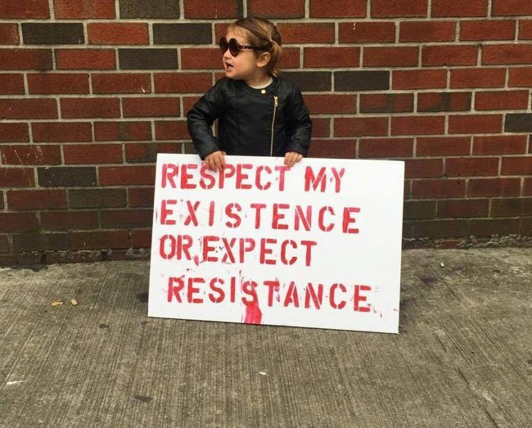 "A girl holding a sign that says ""respect my existence or expect resistance"""