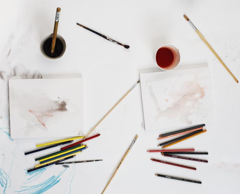 Different art supplies on a white workspace.