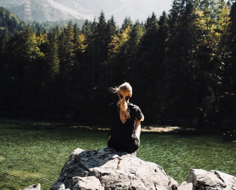 a woman in black shirt sitting on rock near green trees