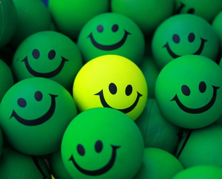 Green rubber balls with smiles.