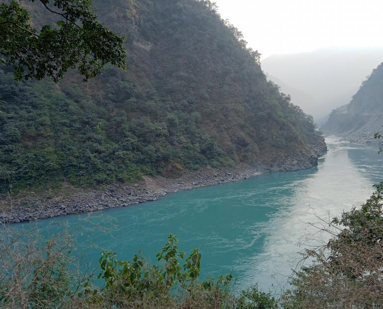 Image of clear water of river Ganga flowing along the base of the mountains.