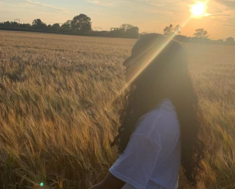 A girl walking on a field with a golden sunset.
