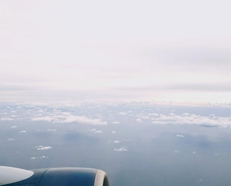 Plane engine over water and clouds