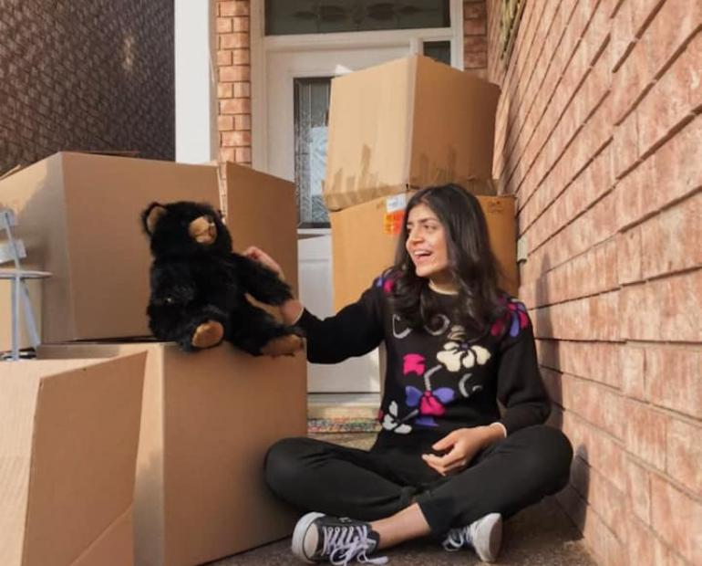 A photo of Aiza sitting next to a stack of boxes filled with teddy bears for children in need.