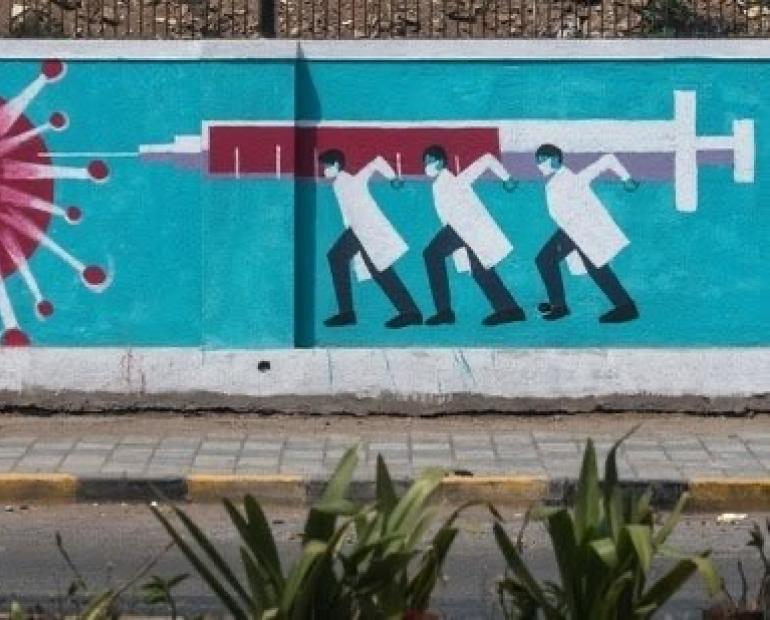People walk past a wall mural depicting medical staff as frontline Covid-19 warriors in Mumbai.