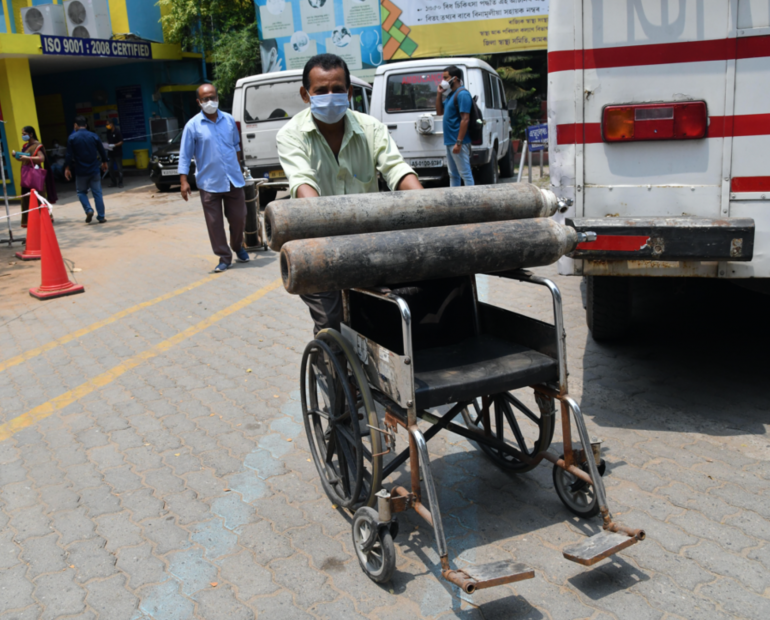 A health worker carries Oxygen cylinder on a wheel chair at MMC Covid hospital in Guwahati on April 30, 2021.