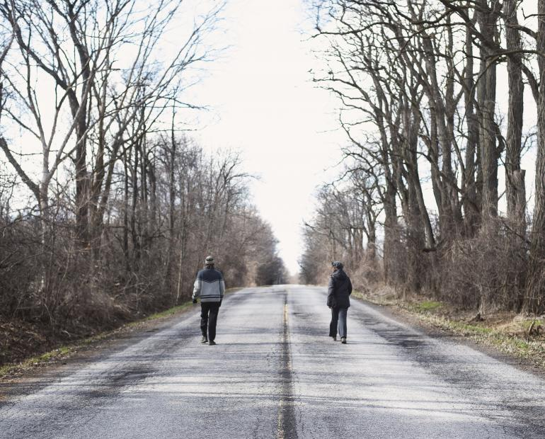 Two people walking on the empty road