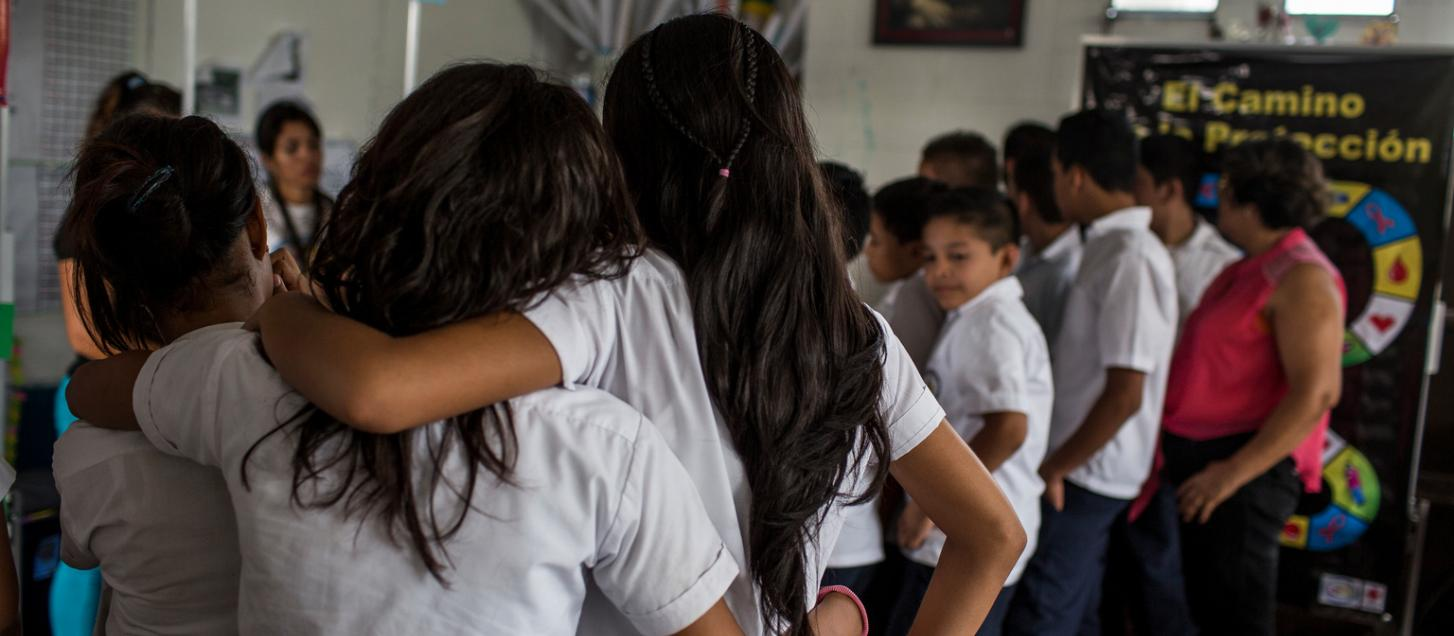 A girl holds her arm over the shoulder of a schoolmate.