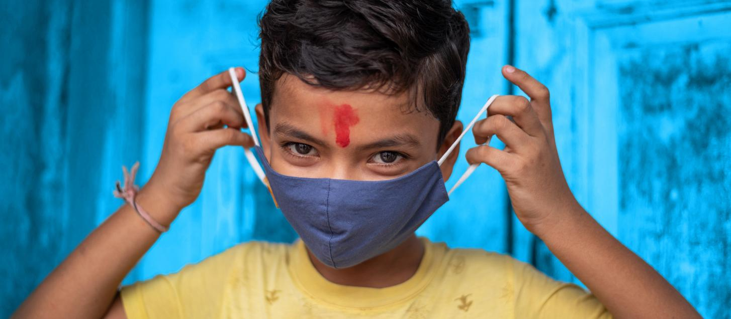 A boy in India teaches of how properly use a mask.